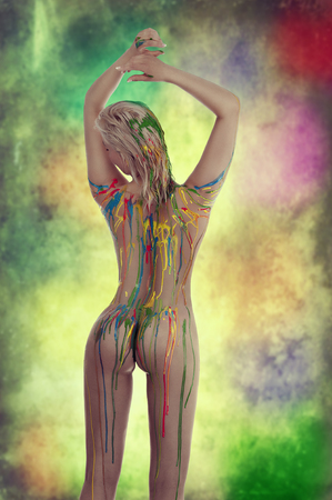 very sensual naked girl with multicolored body paint over her body giving sexy pose against white background. photo