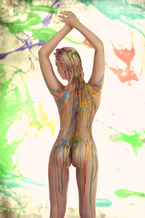 beautiful blond nude girl with multicolored body paint over her body giving sexy pose against white background. photo
