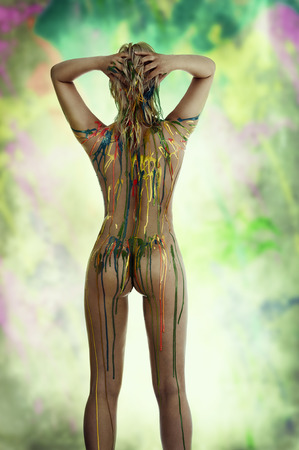 beautiful blond nude girl with multicolored body paint over her body giving sexy pose from back view against white background. photo