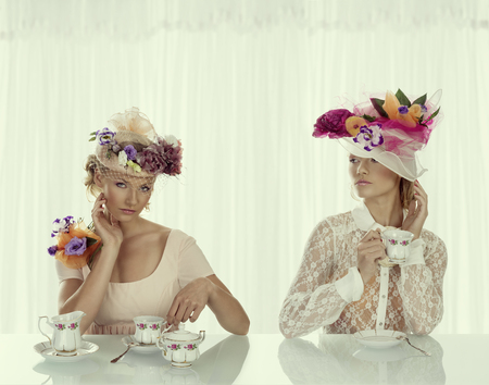 two blonde girl with floral decoration om hat and classical tea set on the table , in high key photo