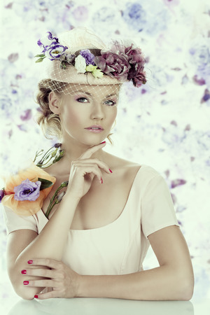pretty blonde girl with flowers on the hat and on the shoulder, she looks in to the lens with the right hand under the chin photo
