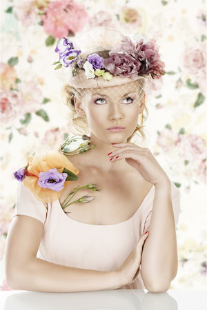 pretty blonde girl with flowers on the hat and on the shoulder, she looks up and her left hand is under the chin photo