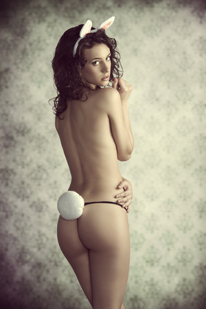 erotic easter shoot of sexy curly brunette woman turned on her back showing her naked body and wearing only funny panties and pink rabbit ears  photo