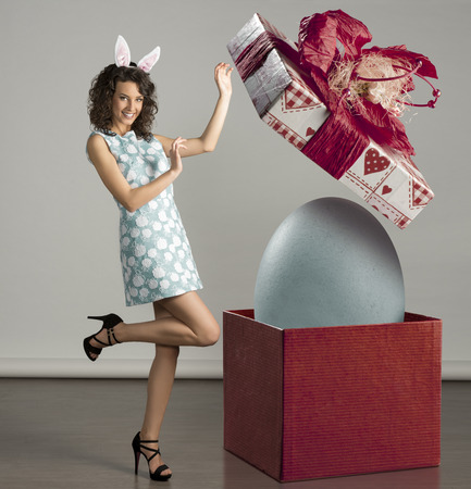 very cute young woman in spring ligh blue dress, with bunny ears, near easter big box with egg inside photo
