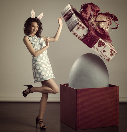 very cute young woman in spring ligh blue dress, with bunny ears, near easter big box with egg inside , grunge color  photo