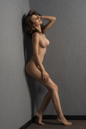 very sensual naked woman , with long hair keeping her body against a wall and looking down. fashion shot