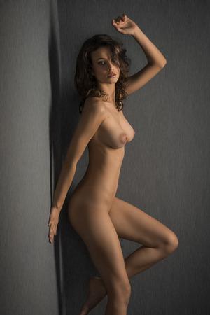 desnudo artistico: belleza sexy mujer desnuda contra la pared gris, posando y mirando a la cámara con ojos sensuales Foto de archivo