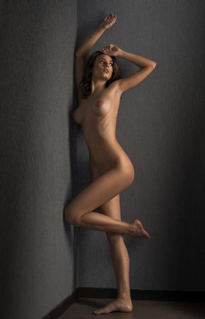 desnudo artistico: desnuda mujer morena joven y bonita, en pose artística contra una pared que muestra su impresionante cuerpo Foto de archivo