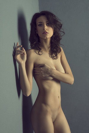 nude: sexy beautiful girl , showing her perfect stunning naked body , near a gray wall and looking in camera  Stock Photo