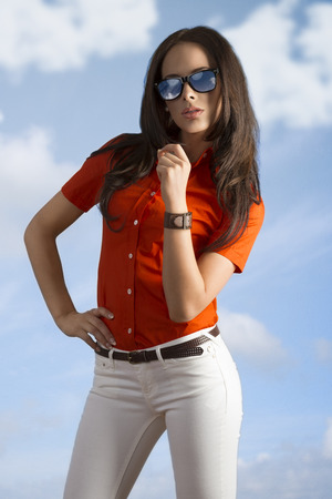 pretty girl with brown hair wearing fashion casual clothes red shirt and white jeans . on blue sky
