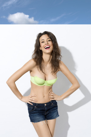 pretty young woman in green bra and shorts , near a white wall giving a great smile to the camera  photo