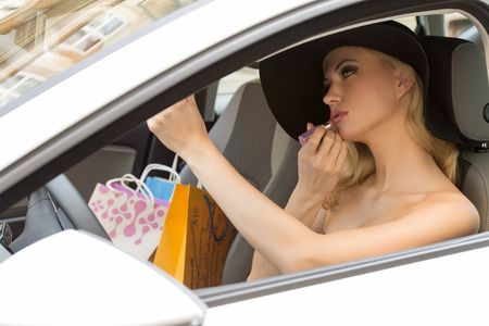 beauty woman sitting in car , with hat and shopping bags near, in act to make up her lips. photo