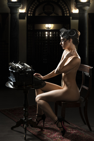 vintage shot of a naked woman sitting on desk and typing on an old fashion type-writer with light effect photo