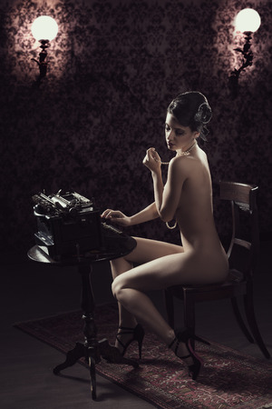 vintage shot of a naked woman sitting on desk and typing on an old fashion type-writer in dark background photo