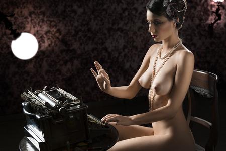 mujer desnuda sentada: tiro del vintage de una mujer desnuda sentada en el escritorio y escribiendo en una vieja moda máquina de escribir en fondo oscuro