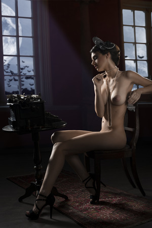 naked woman sitting: vintage shot of a naked woman sitting on desk and typing on an old fashion type-writer in dark background