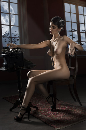 erotic fantasy: vintage shot of a naked woman sitting on desk and typing on an old fashion type-writer in dark background