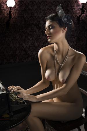 desnudo artistico: tiro del vintage de una mujer desnuda sentada en el escritorio y escribiendo en una vieja moda máquina de escribir en fondo oscuro