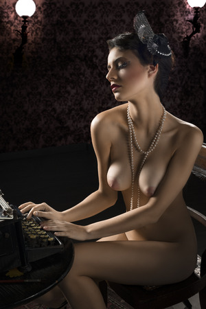 vintage shot of a naked woman sitting on desk and typing on an old fashion type-writer in dark background