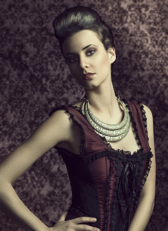 portrait of beautiful young woman in elegant old fashion purple dress , and a very importatnt necklace. hairdo. photo