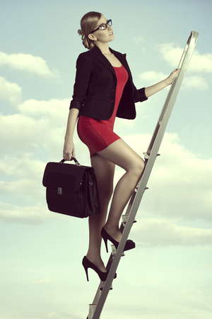upstairs: pretty business woman with work bag stepping ladder of the success with ambition