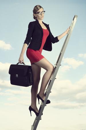 subir escaleras: sexy mujer de negocios joven que recorre en escalera con traje corto y bolsa de trabajo