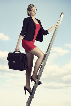sexy young business woman walking on staircase with short suit and work bag  Stock Photo