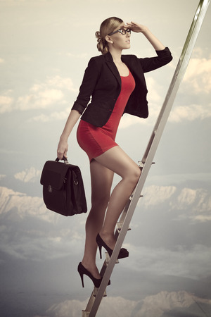 sensual business woman climbing ladder with sexy suit and work bag, looking in front of her with conviction