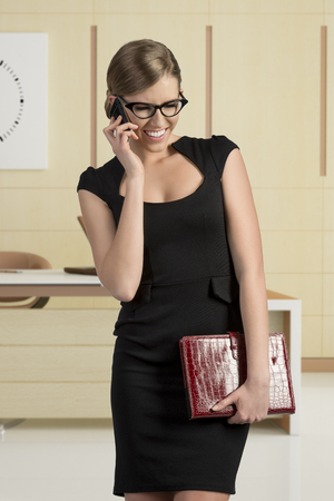 business blond woman in black dress talking at mobile and wearing fashion eye glasses smiling photo
