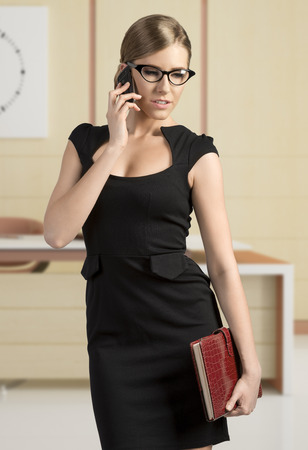 business blond woman in black dress talking at mobile and wearing fashion eye glasses  photo