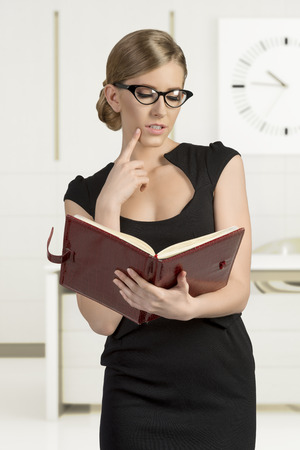 business blond woman in black dress reading agenda and wearing fashion eye glasses  photo
