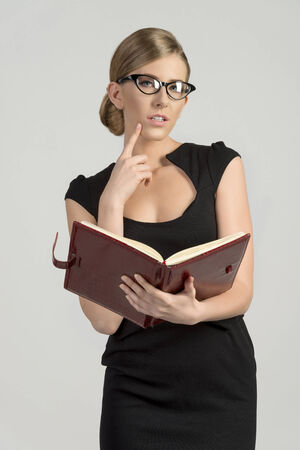 business blond woman in black dress with agenda and wearing fashion eye glasses looking in camera photo