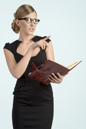 business blond woman in black dress with agenda and wearing fashion eye glasses looking one side photo