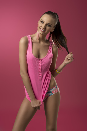 smiling sexy brunette girl posing with pink sexy style, colorful panties, wrist watch and ponytail. Fresh sensual portrait  photo