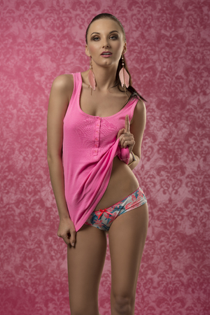 woman panties: brunette woman with sexy fashion lingerie wearing pink shirt and colorful panties, posing with her perfect body and brown ponytail