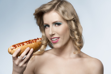 sexy food: close-up portrait of sensual blonde female with fashion style, cute make-up and curly blonde hair-style posing with hot-dog in the hand