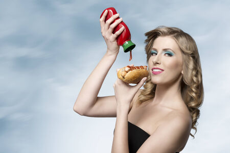 hungry girl with fashion look posing with curly blonde hair putting tomato ketchup on her hot-dog  photo