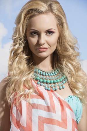 pareo: close-up portrait of pretty girl with summer style, blonde hair, pareo and turquoise necklace. woman  in vacation