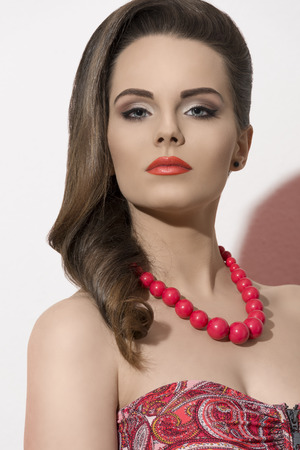 fashion close-up shoot of sexy woman with elegant hair-style, cute make-up and red necklace  photo