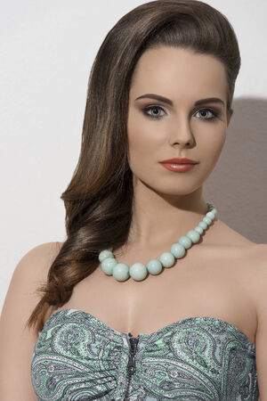 sensual girl with summer fashion style posing with elegant smooth hair-style, cute make-up and green necklace   photo