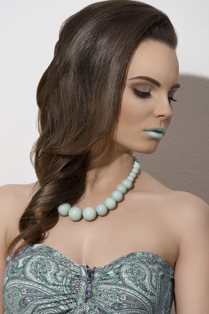 cute young brunette lady posing in close-up fashion shoot with cute smooth elegant hair-style, make-up and green necklace  photo