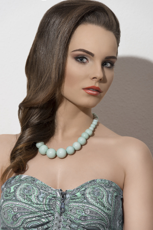 fashion summer shoot of cute brunette girl posing with smooth hair-style, make-up and green necklace  photo