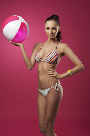 fashion shoot: summer shoot of sexy lady posing with bikini, ponytail, yellow fashion wrist watch and pink beach ball in the hand