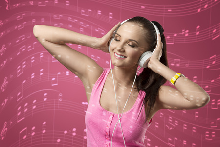 white singlet: happy woman with headphone listening music and smiling, wearing pink singlet