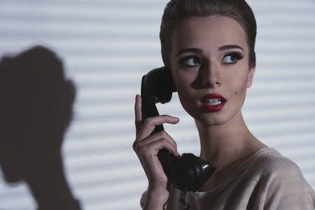 vintage woman with elegant hair-style and worried expression talking on the retro phone  photo