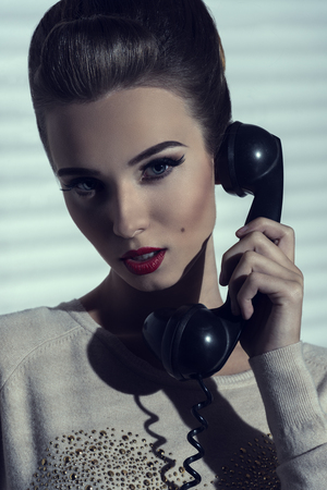 close-up shoot of charming elegant lady talking on vintage phone with receiver  photo