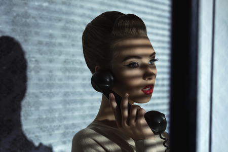 fashion shoot of vintage girl talking on phone with retro receiver in half-light atmosphere  photo
