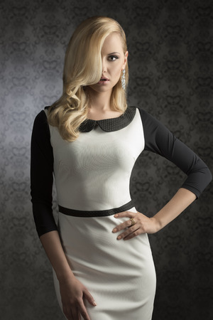 sensual lips: elegant fashion lady with elegant look, long blonde hair and shiny jewels wearing black and white dress