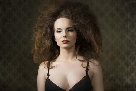 voluminous: fashion shoot of sensual brunette woman with voluminous creative hair-style, black bra and cute make-up
