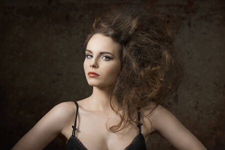 voluminous: sexy girl with charming expression wearing black bra and posing with voluminous creative hair-style